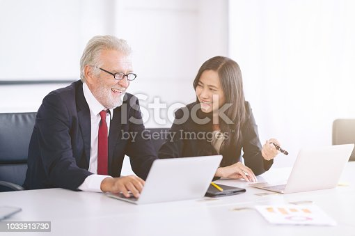 istock Smile Creative woman working on laptop computer with partner at desk office 1033913730