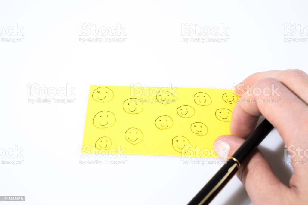 Smile draw with hand and a pen on a yellow paper composition stock photo