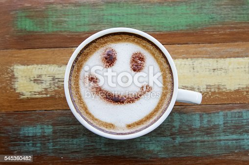 istock Smile face drawing on latte art coffee , wood color background 545360482