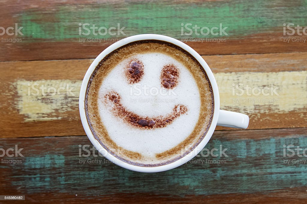 Smile face drawing on latte art coffee , wood color background stock photo