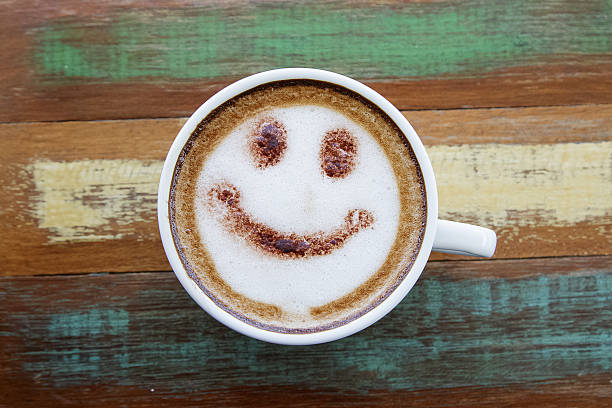 Smile face drawing on latte art coffee , wood color background - foto de stock