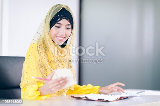 istock Smile Female arab take note on working space.Arabian Businesswoman plan buy property concept 1033913062