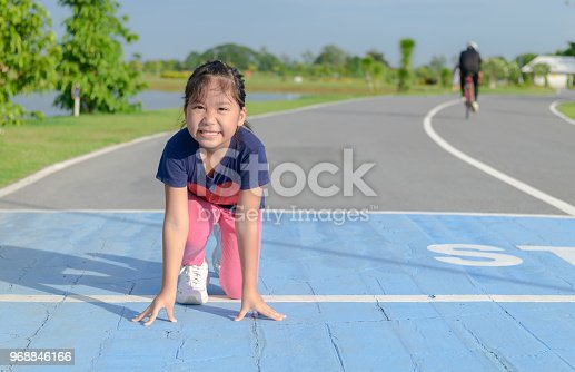 Smile cute girl in ready position to run on track, sport and healthy concept.