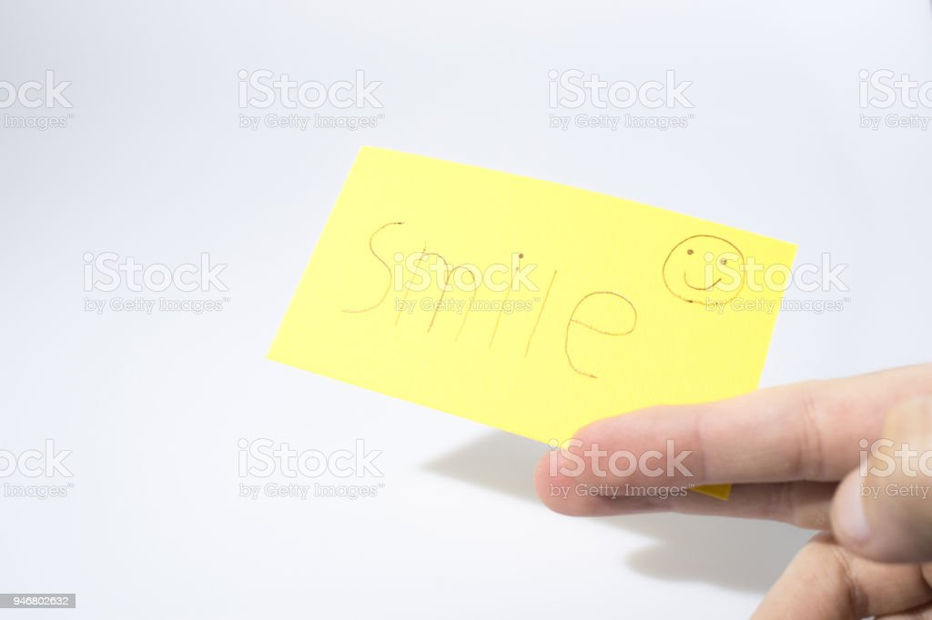 Smile handwrite with a hand and a smile on a yellow paper compsoition stock photo
