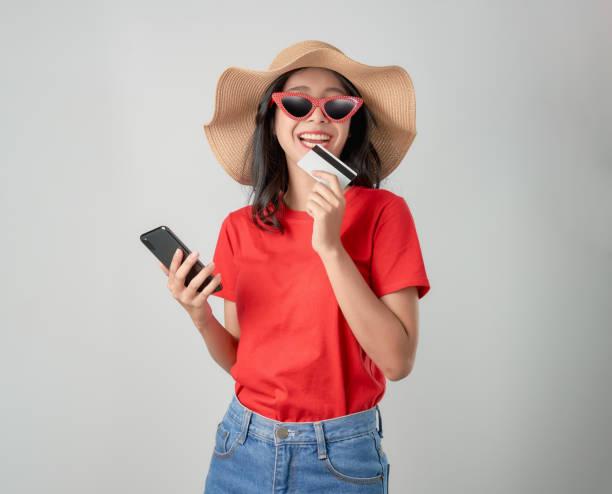lächeln glücklich asiatische frau rotes t-shirt hält smartphone und kreditkarte online-shopping auf grauem hintergrund. - damen shirts online stock-fotos und bilder