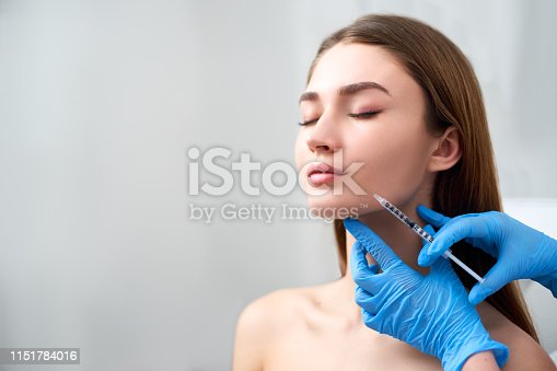 Smile lifting and lip augmentation. Beautician doctor hands doing beauty procedure to female face with syringe. Young woman's mouth countouring with filler injection. Marionette lines treatment in cosmetology clinic.