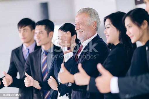 istock Smile Manager in center professional Team.Successful Cooperation Organization People Concept.Peopel Business Team show thumbs up standing in conferace room 1038332358