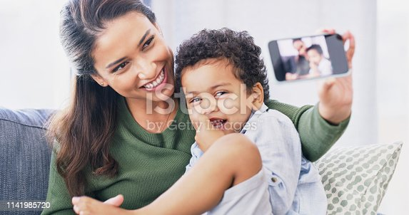 Cropped shot of an attractive young woman and her son taking selfies in their living room