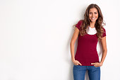Pleasant young woman smiling on white wall with copy space