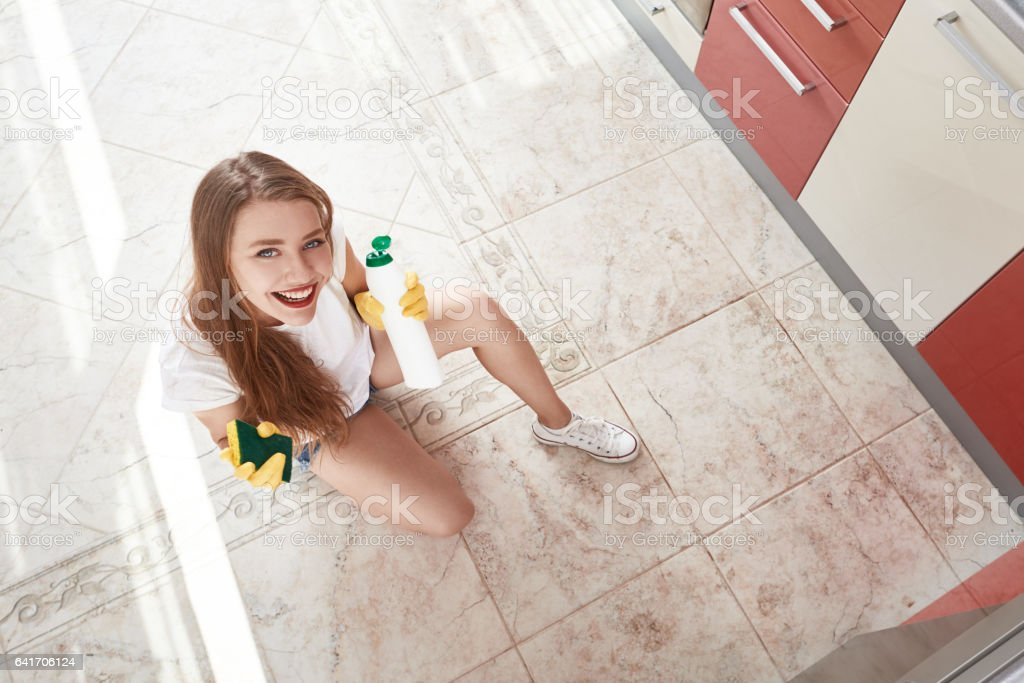 high angle view of young woman smiling while cleaning the kitchen...