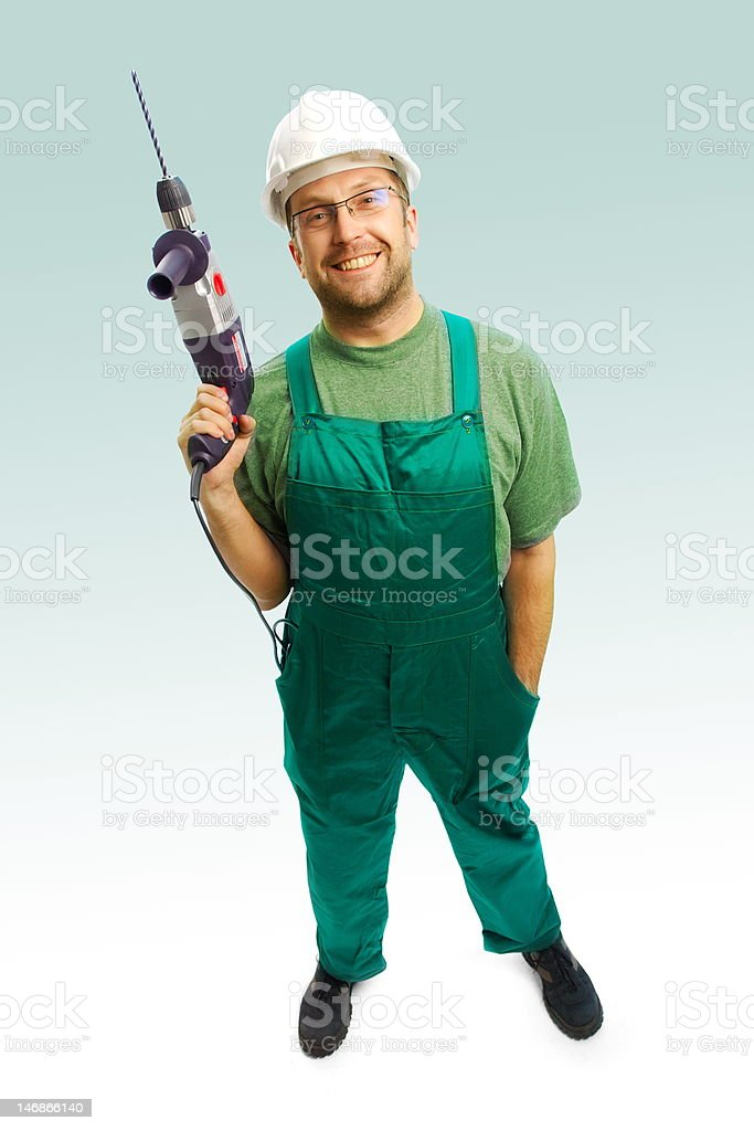 Smiled workman in helmet and overalls with drill royalty-free stock photo