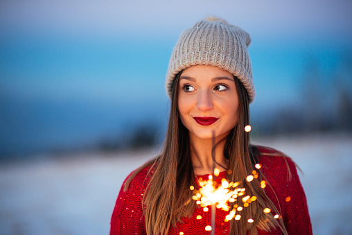 Portrait of a wonderful young woman holding a sparkling stick.