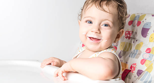 Smiley baby girl in baby chair stock photo