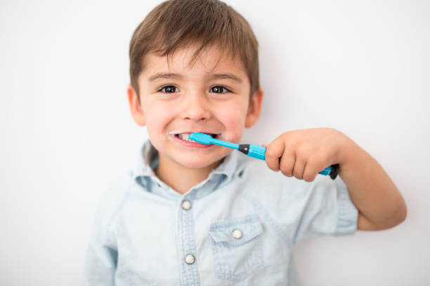 smiley boy cleans a teeth isolated on grey background A smiley boy cleans a teeth isolated on grey background dental health stock pictures, royalty-free photos & images