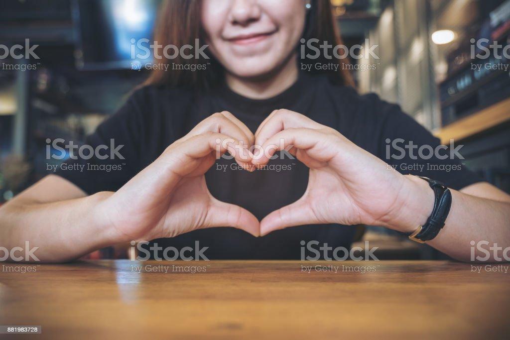Bir gülen yüz Asyalı kadın yapma kalp el işareti ile duygu Inlove stok fotoğrafı