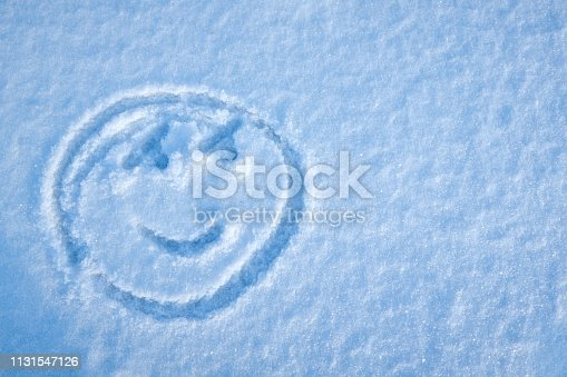Smiley face drawing in the snow on a sunny winter day. copy space