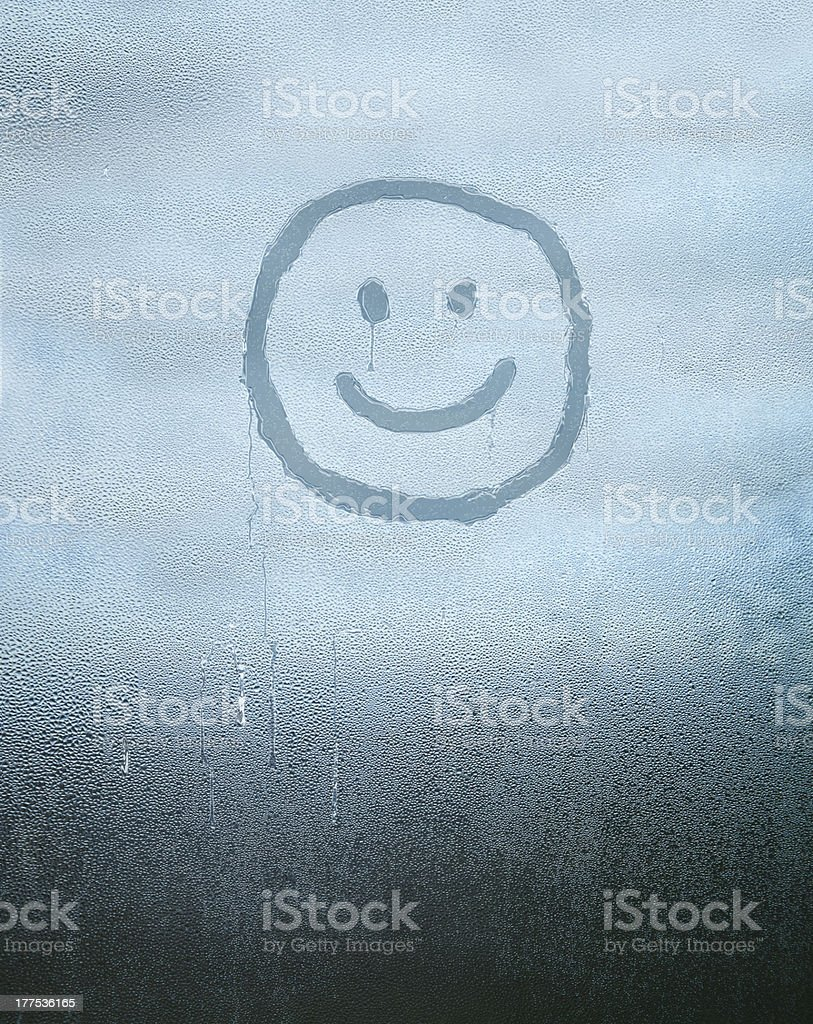 Smiley face drawn over condensated glass stock photo