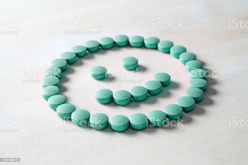 Smiley face from pills on wooden table. Happy and positive feeling from successful healing process or satisfied with health care and doctor services. Correct medication or right medical treatment. stock photo