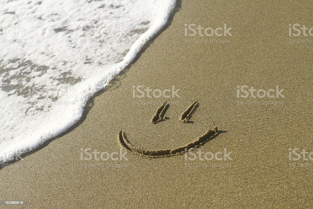 Smiley face on a beach next to a wave stock photo
