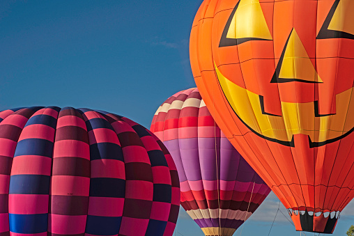 Set of three hot air balloons against a blue sky.