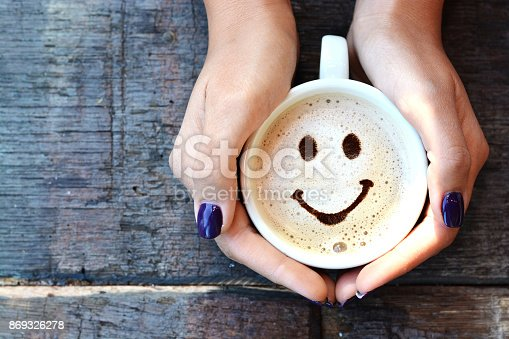 istock Smiley face on cappuccino foam, woman hands holding one cappuccino cup on wooden table 869326278