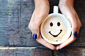Smiley face on cappuccino foam, woman hands holding one cappuccino cup on wooden table