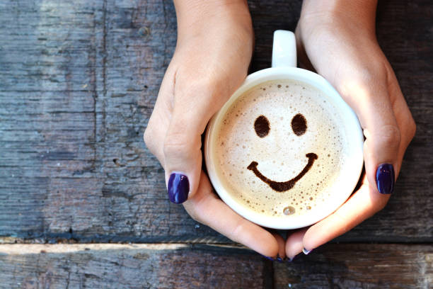smiley face on cappuccino foam, woman hands holding one cappuccino cup on wooden table - coffee stock pictures, royalty-free photos & images