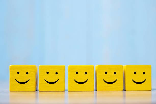smiley-gesicht auf gelbem holzwürfel. service-bewertung, ranking, kundenbewertung, zufriedenheit s.a. - feedback stock-fotos und bilder