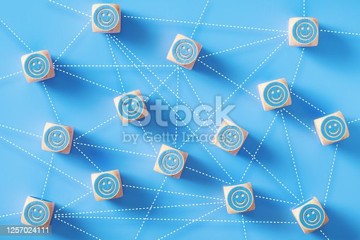 Smiley face symbols drawn blue wood blocks which are connected by dotted lines sitting on blue background. Horizontal composition with copy space. Social media and networking concept.