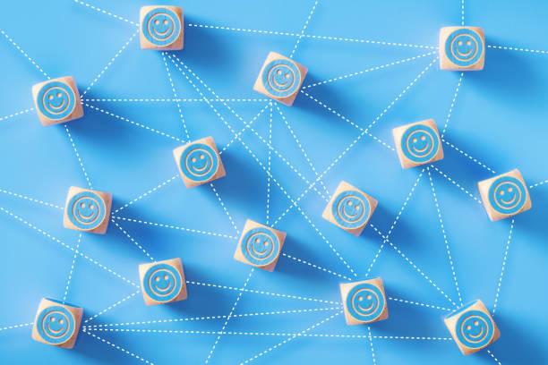 smiley gesicht symbole gezeichnet blau holz blöcke, die durch gepunktete linien sitzen auf blauem hintergrund verbunden sind - feedback stock-fotos und bilder