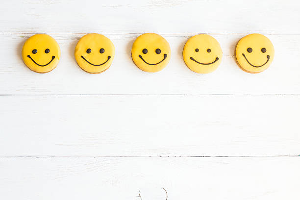 Smiley faces on wooden white background. Top view, flat lay - Photo