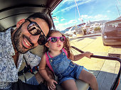 Smiley father with adorable daughter drive with golf car
