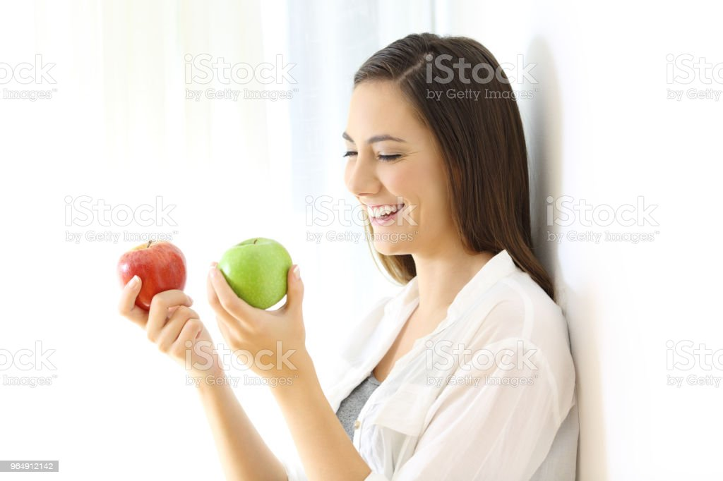 Smiley girl holding two red and green apples royalty-free stock photo