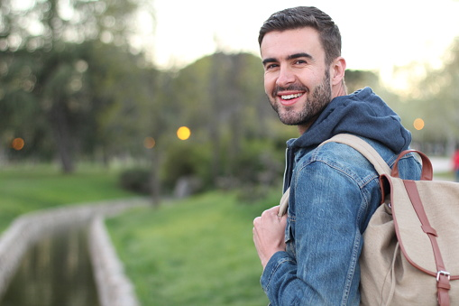 istock Smiley male holding backpack outdoors with copyspace 679882360
