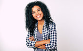 istock Smiley mood. Good-looking African American girl in casual outfit is laughing while looking at the camera, slightly turning her head on the left, with her arms folded. 1180642199