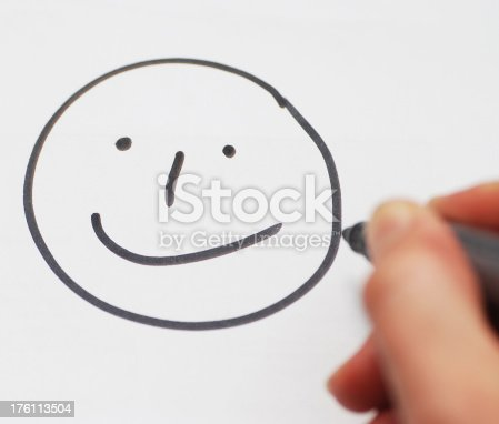 istock smiley on white paper painted with hand 176113504