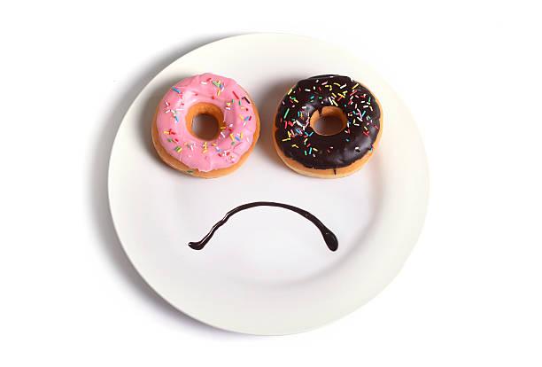 smiley-Gesicht auf Gericht mit traurigen Augen Schokolade köstlichen donuts – Foto