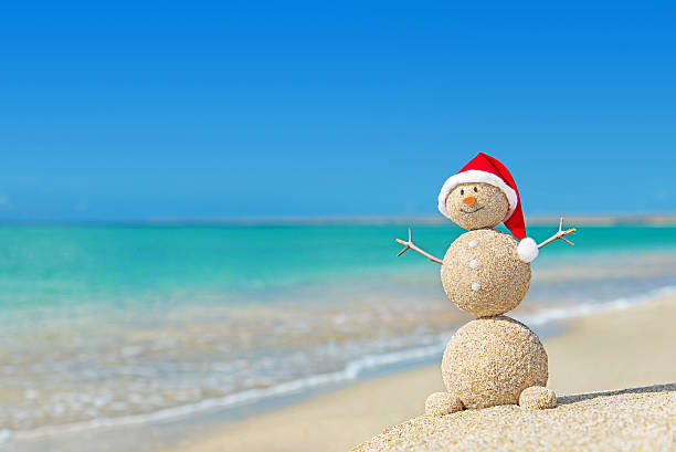 Smiley sandy snowman in santa hat. Holiday Christmas concept stock photo