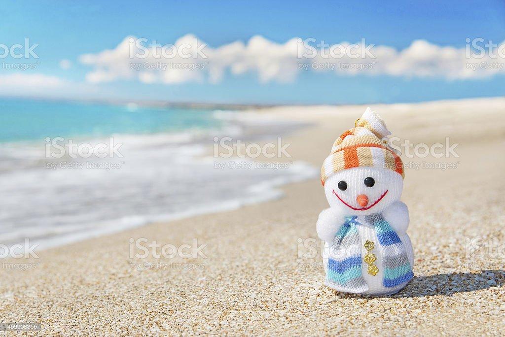 Smiley toy christmas snowman at hot sea beach. stock photo