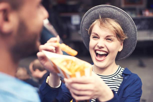 smiley frau kümmert sich mit ihrem partner - streetfood stock-fotos und bilder