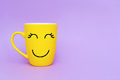 Smiley yellow coffee cup on purple background. Happy friday word concept. Minimalism style, romantic mood, good morning, happiness, break time.