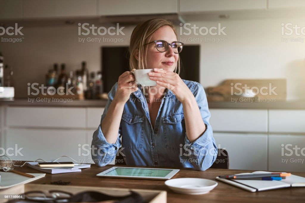 Smiliing woman drinking coffee while working online from home royalty-free stock photo