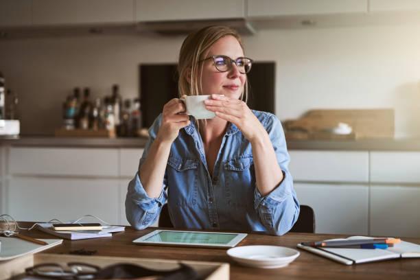 smiliing mujer tomando café mientras trabaja en línea desde casa - café bebida fotografías e imágenes de stock