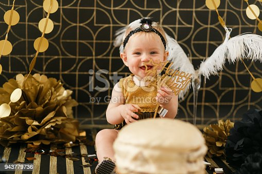 istock Smilin baby holding wooden Happy birthday sign. Cake in front 943779736