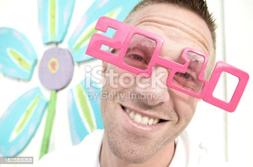 Smiling guy in pink 2010 sunglasses stands in front of bright flower wall