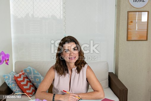 Mature woman studying at her home office.