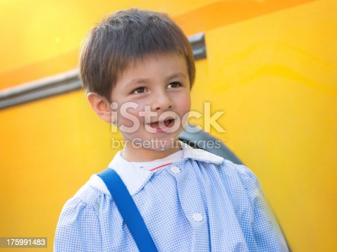 3-4 years-old Child in front a school bus