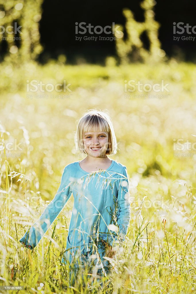 Smiling 5-year-old blonde girl running through long grass stock photo