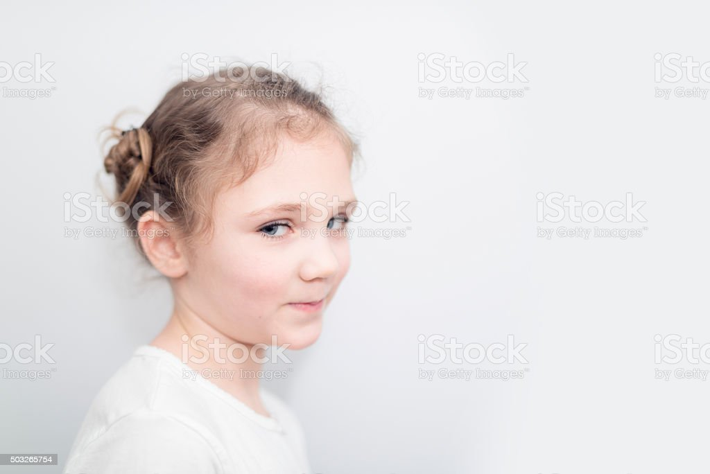 smiling 6 year old blond girl on white background stock photo