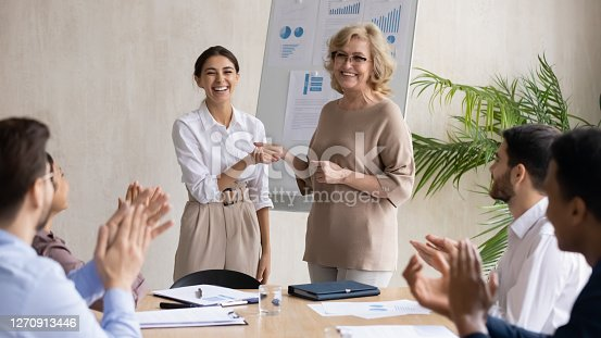 Smiling middle aged 60s female company leader shaking hands with happy young arabic colleague, praising for good work or thanking for good job done at briefing meeting with diverse employees.